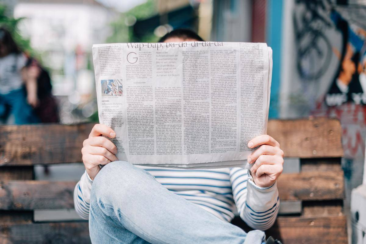person in striped shirt sitting on bench reading newspaper covering face