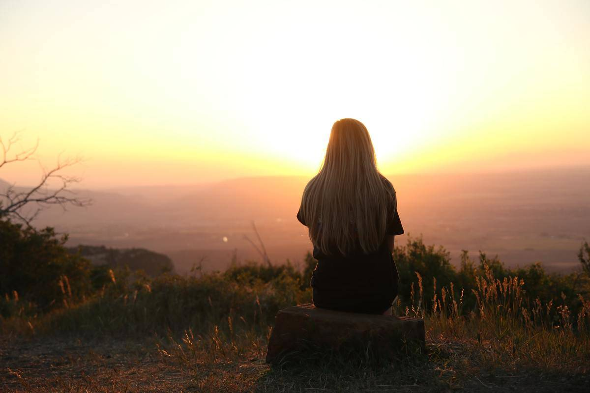 woman seated on hill watching sunset