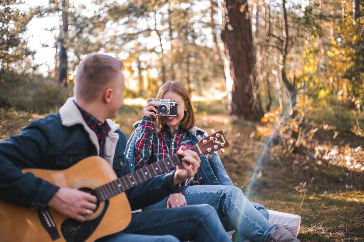 man playing guitar woman taking photo with camera outside