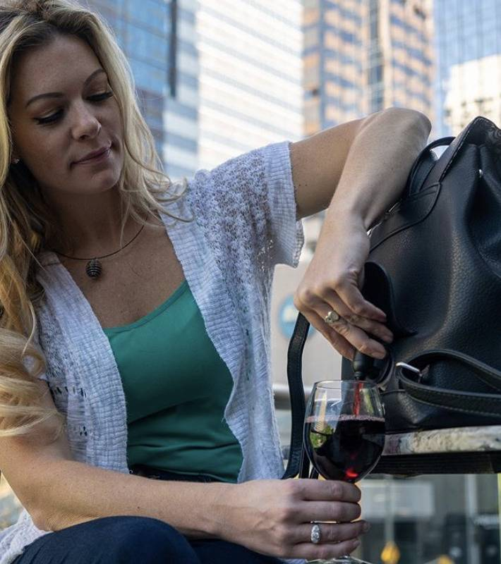 woman using wine tap in city