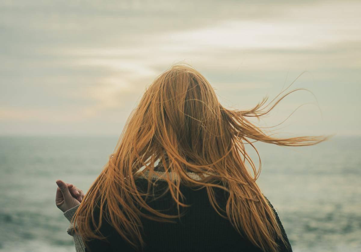woman facing away toward ocean