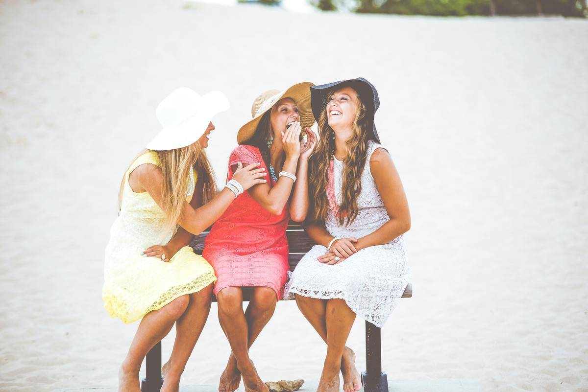 three women in sunhats seated on bench at beach laughing whispering