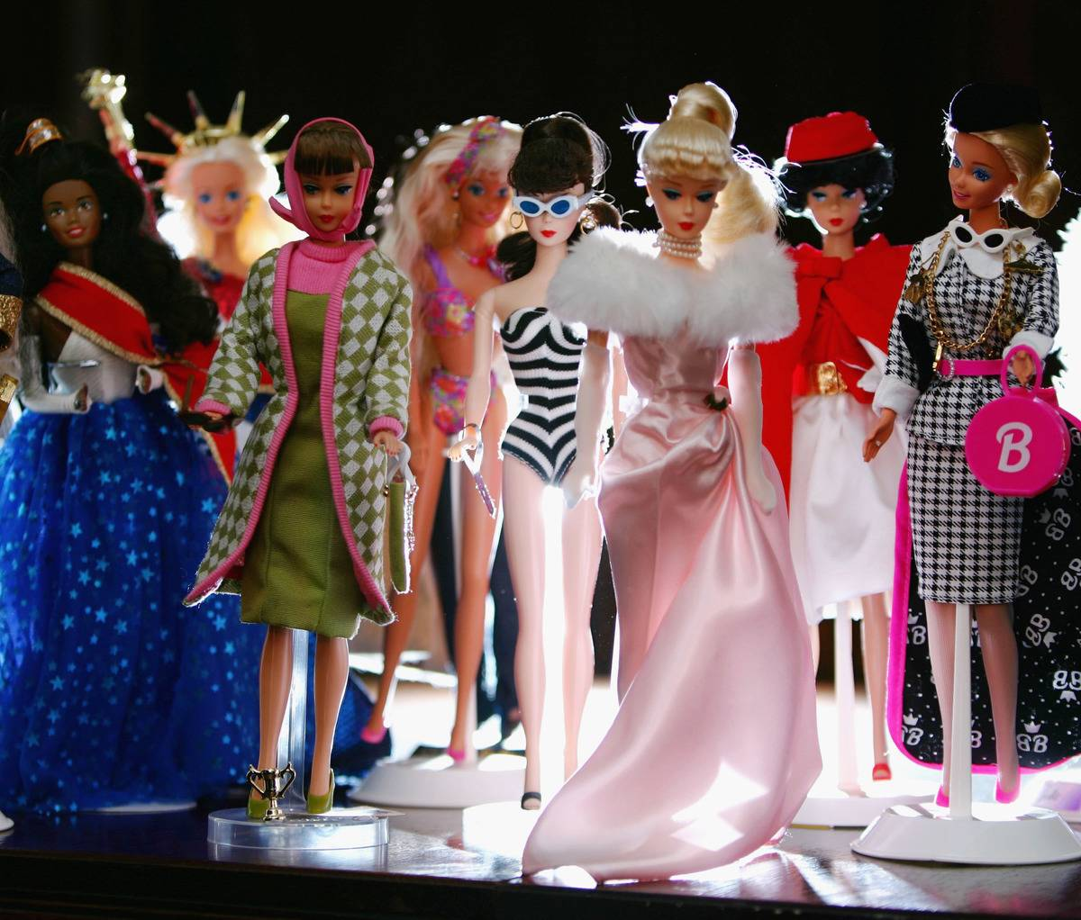 a bunch of different Barbies standing around