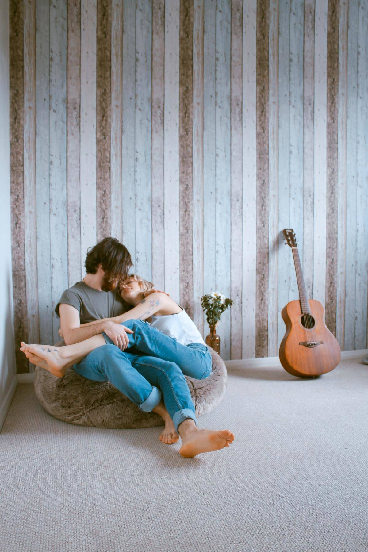 man and woman sit on the couch by a guitar and striped wall