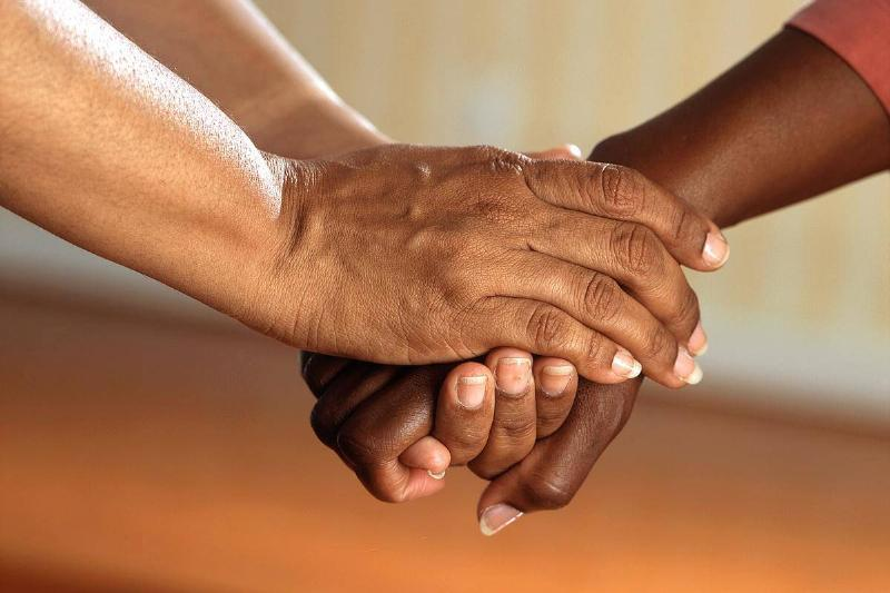 People holding hands in comforting way