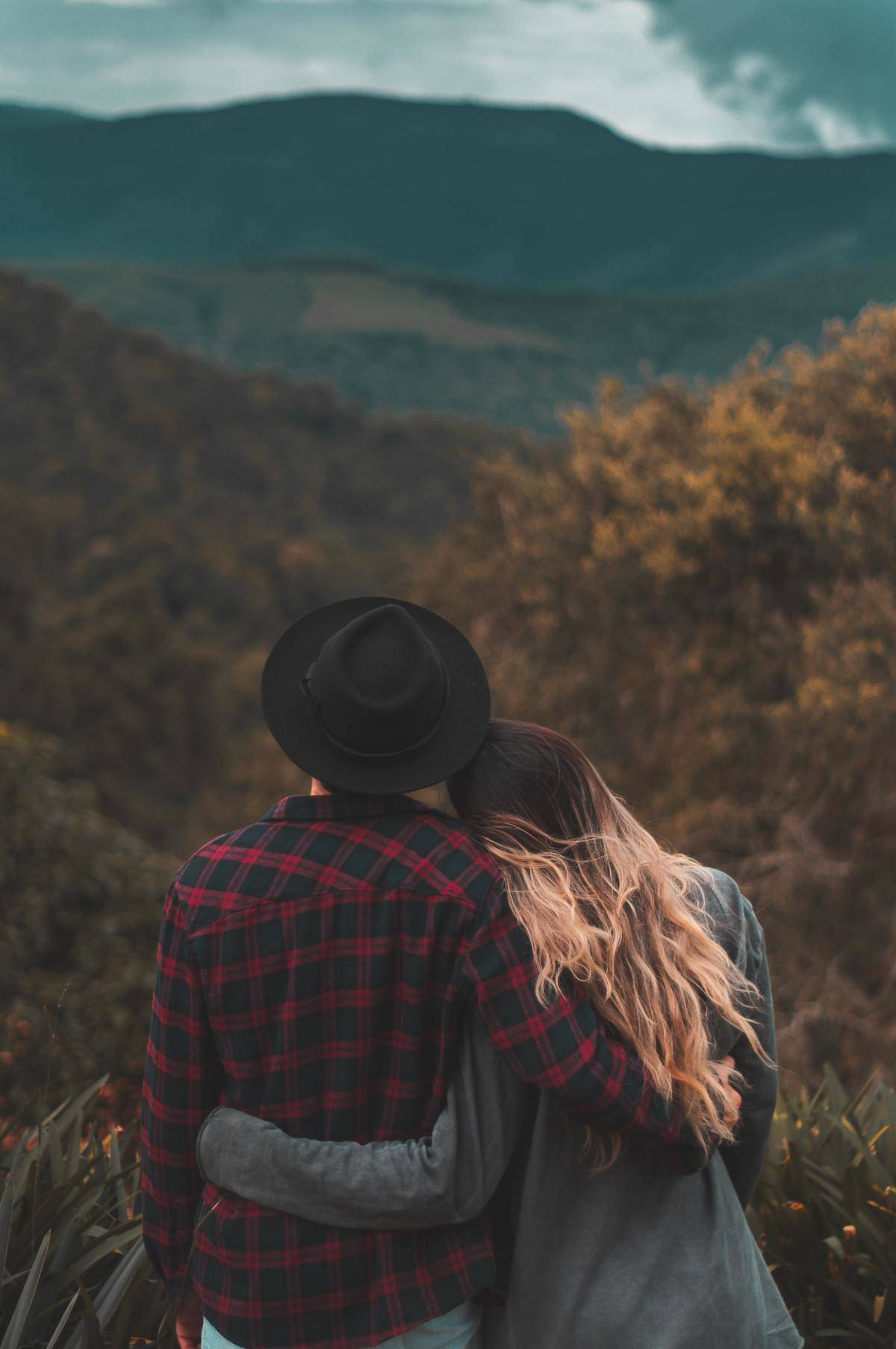 a couple looking out over the view of a forest