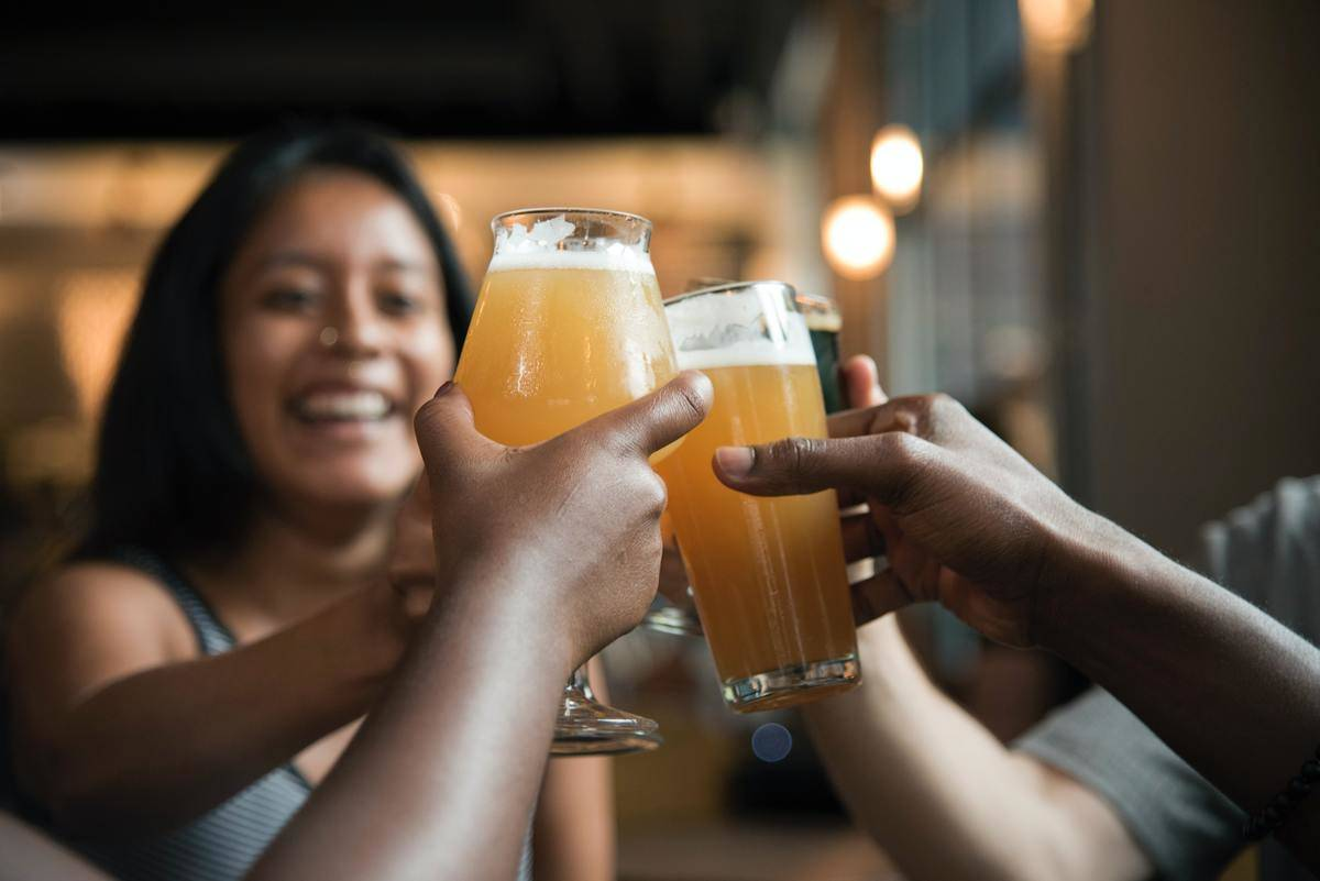 group of friends clink their beer glasses