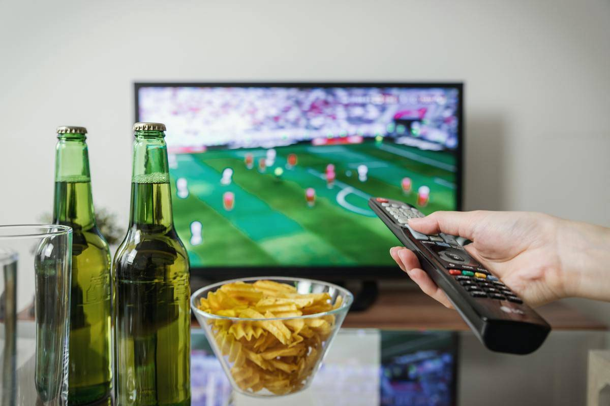 person holding TV remote pointed at soccer game on TV, with beer and chips in the foreground