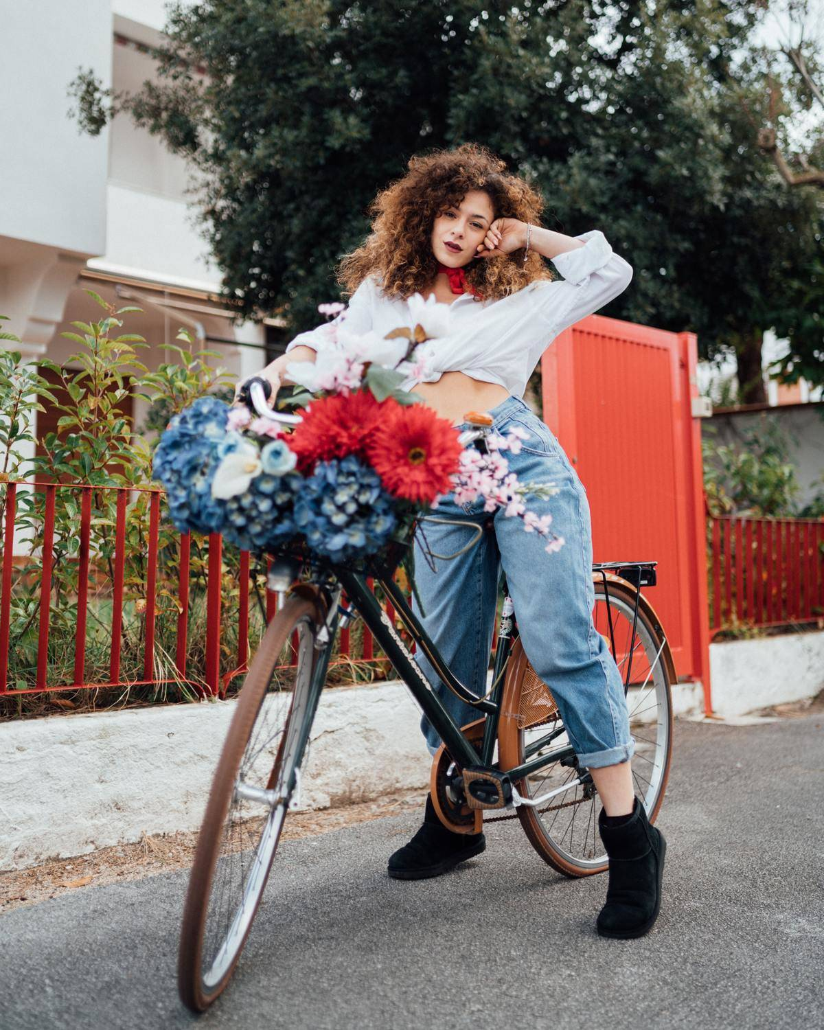 woman riding a bike with a bunch of flowers on it