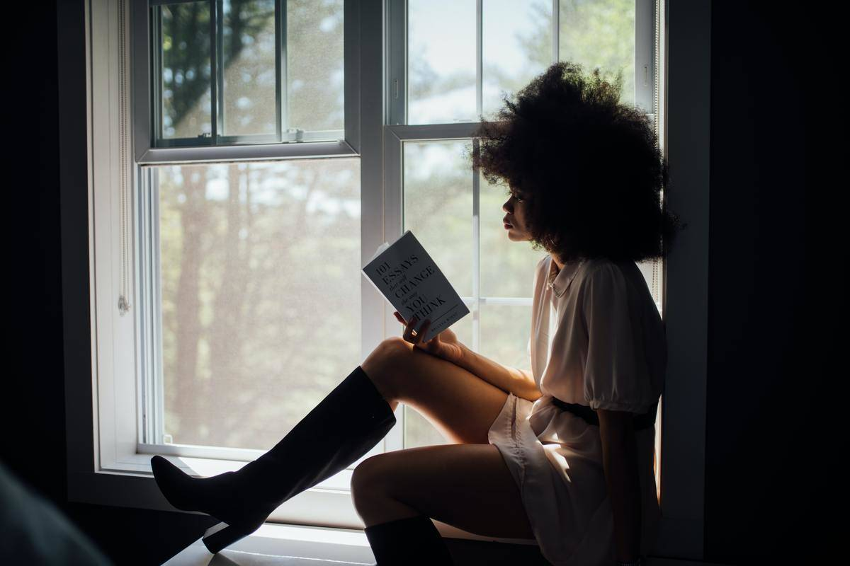 woman sitting by a window trying to read