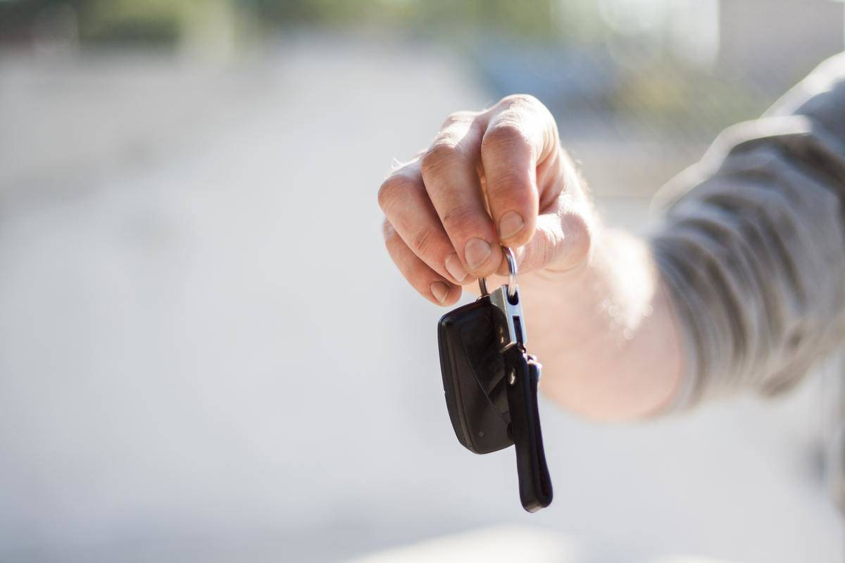 man holding out set of car keys