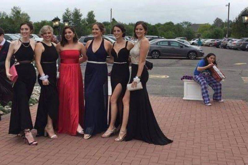 woman eating chips behind a bunch of girls dressed up for prom