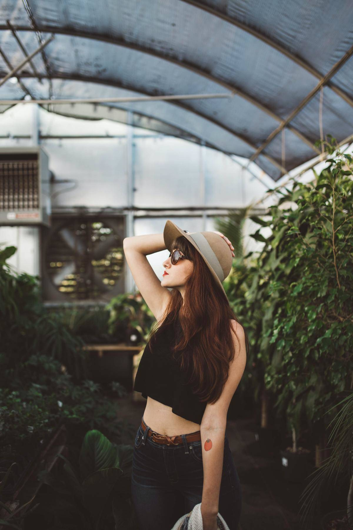 woman poses in greenhouse with glasses and hat