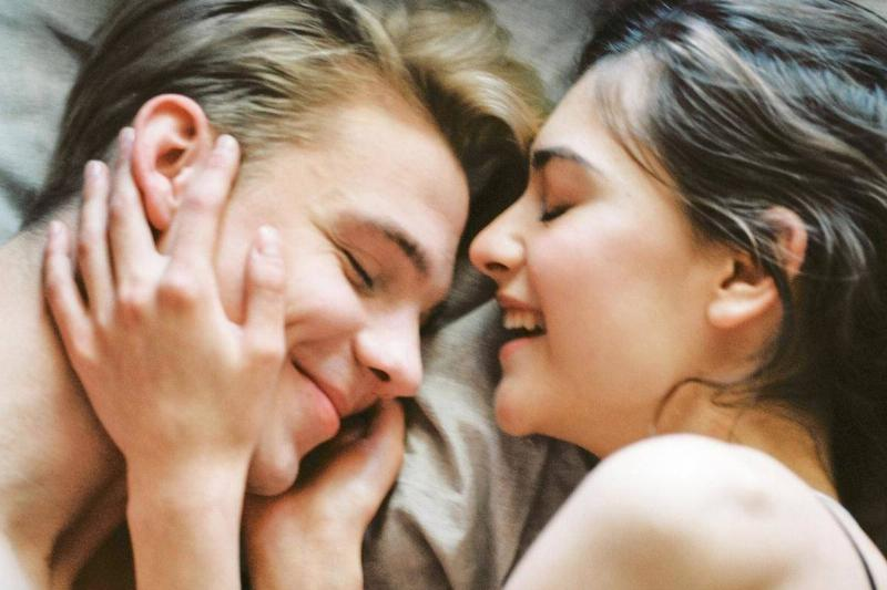 woman holds man's face as they both smile under the sheets