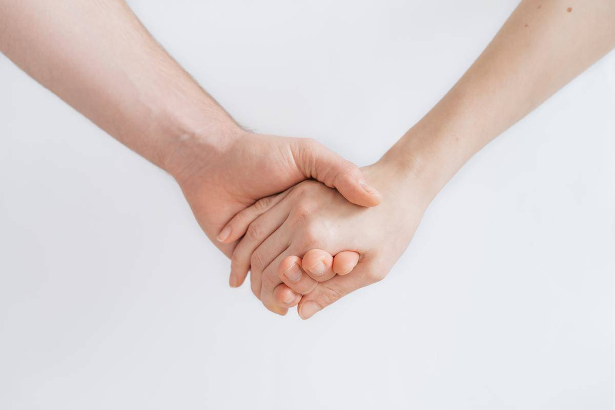 two hands hold each other in a close up