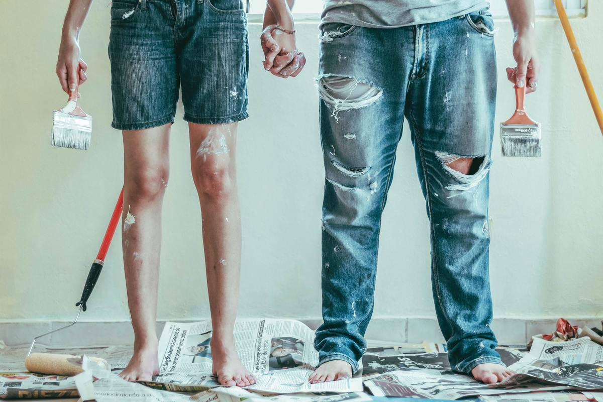 couple holds hands while painting