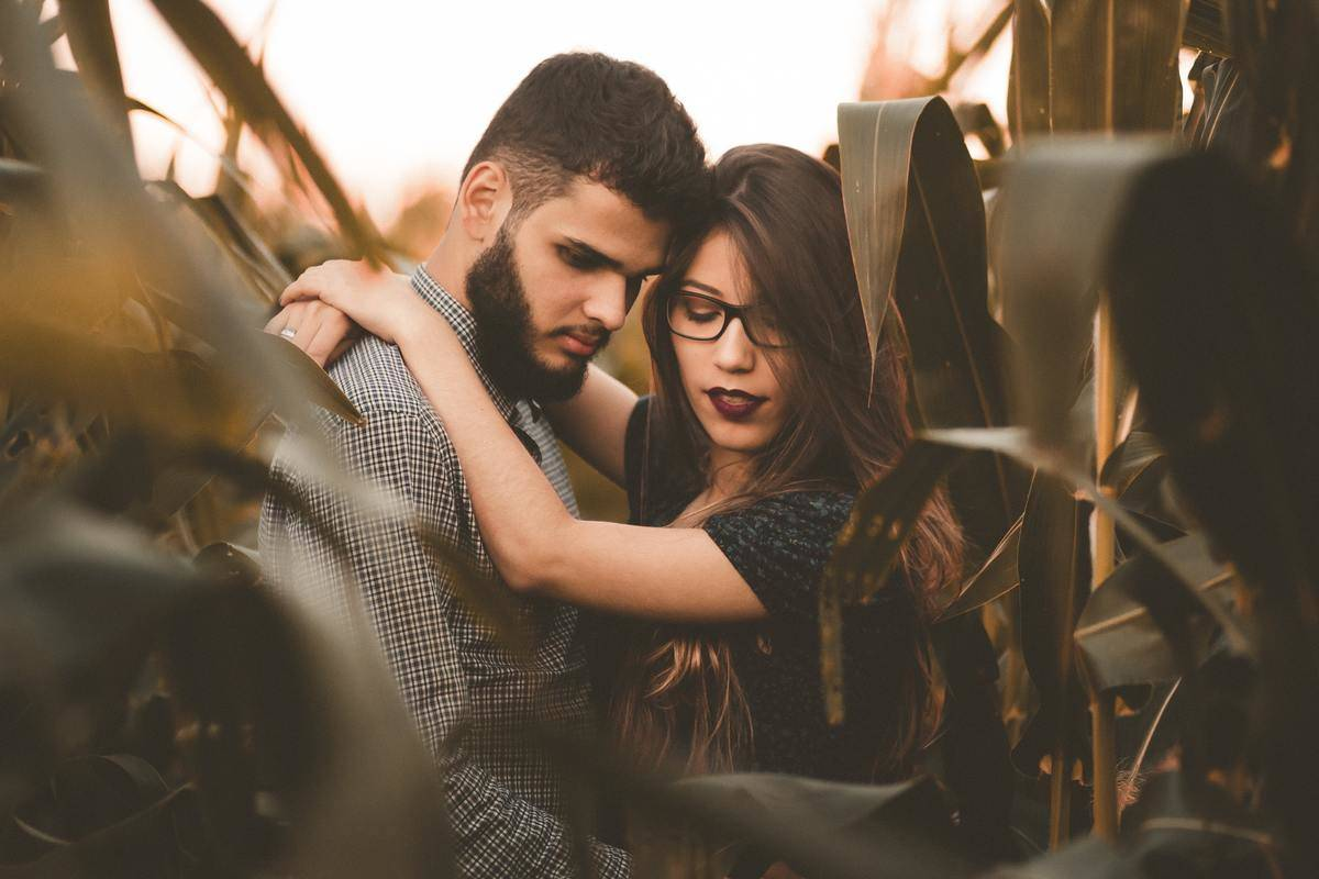 couple hugging in corn field looking down serious