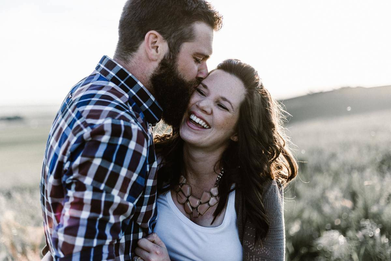 woman laugh as man kisses her cheek