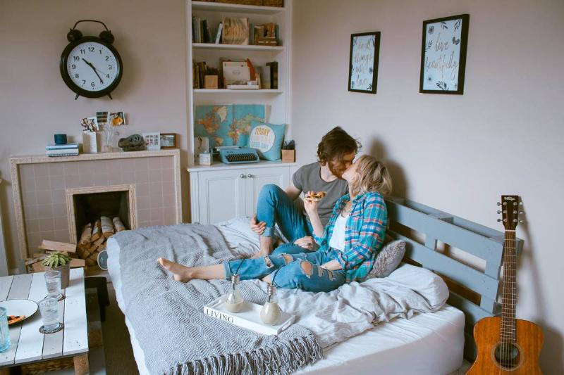 couple kiss in bed while eating breakfast