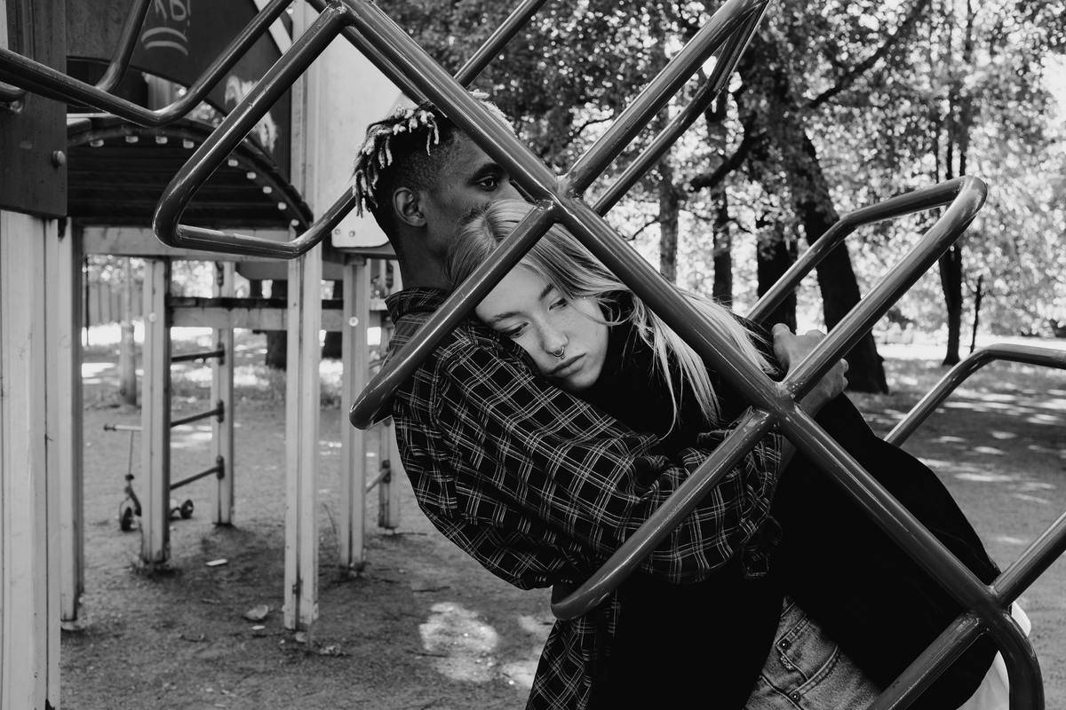 woman leaning on man lying on monkey bars black and white