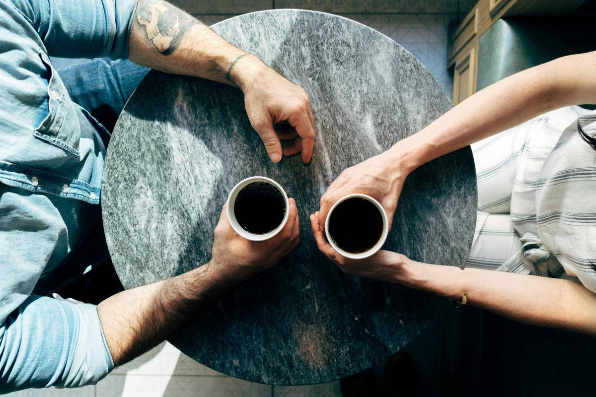top-down view of a couple holding coffee cups