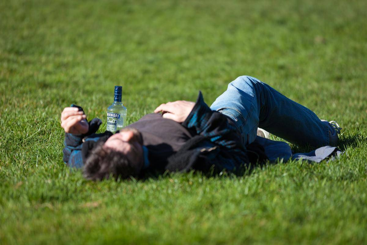 man lying drunk on ground with bottle