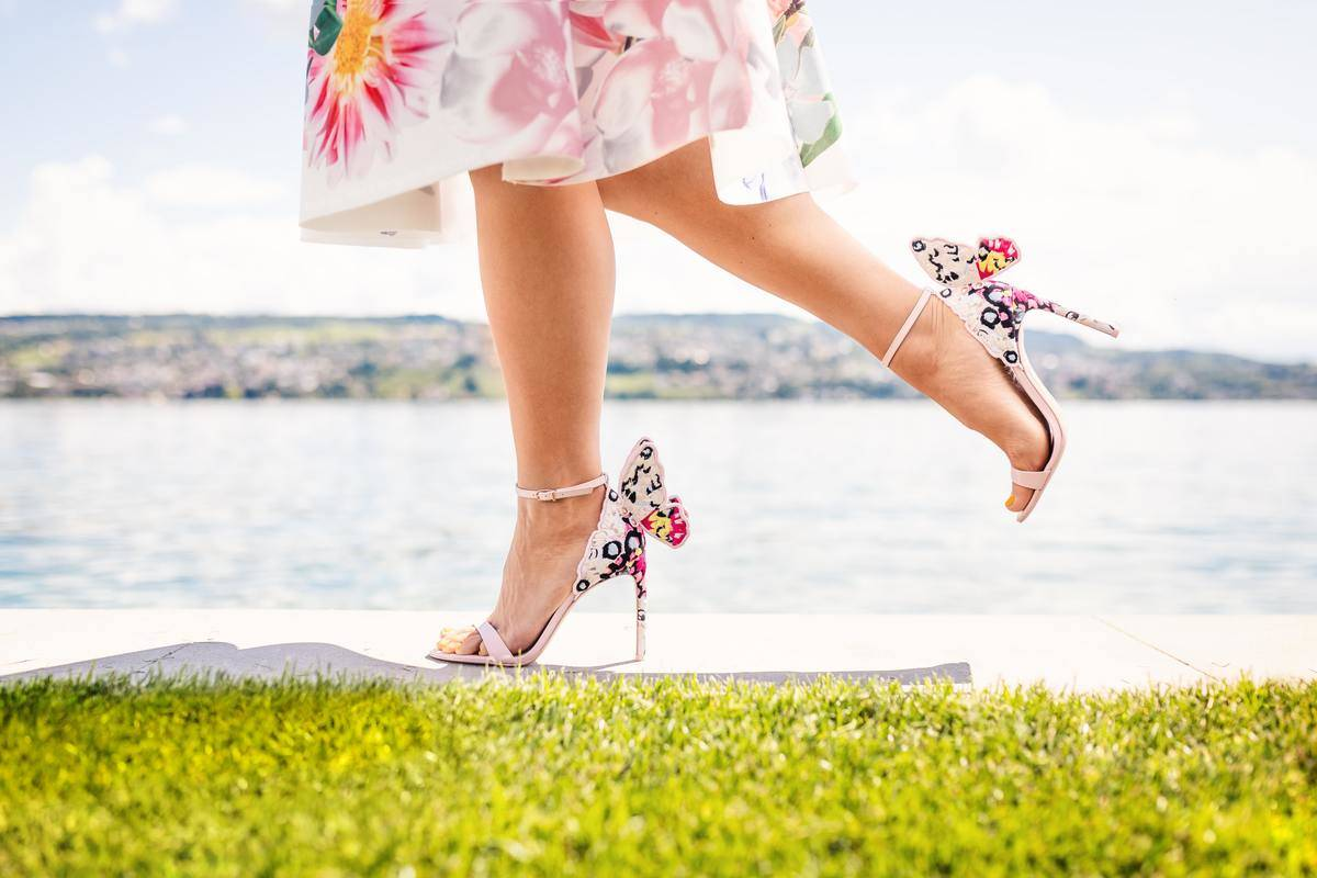 close-up of floral dress and heels walking on grass by the water