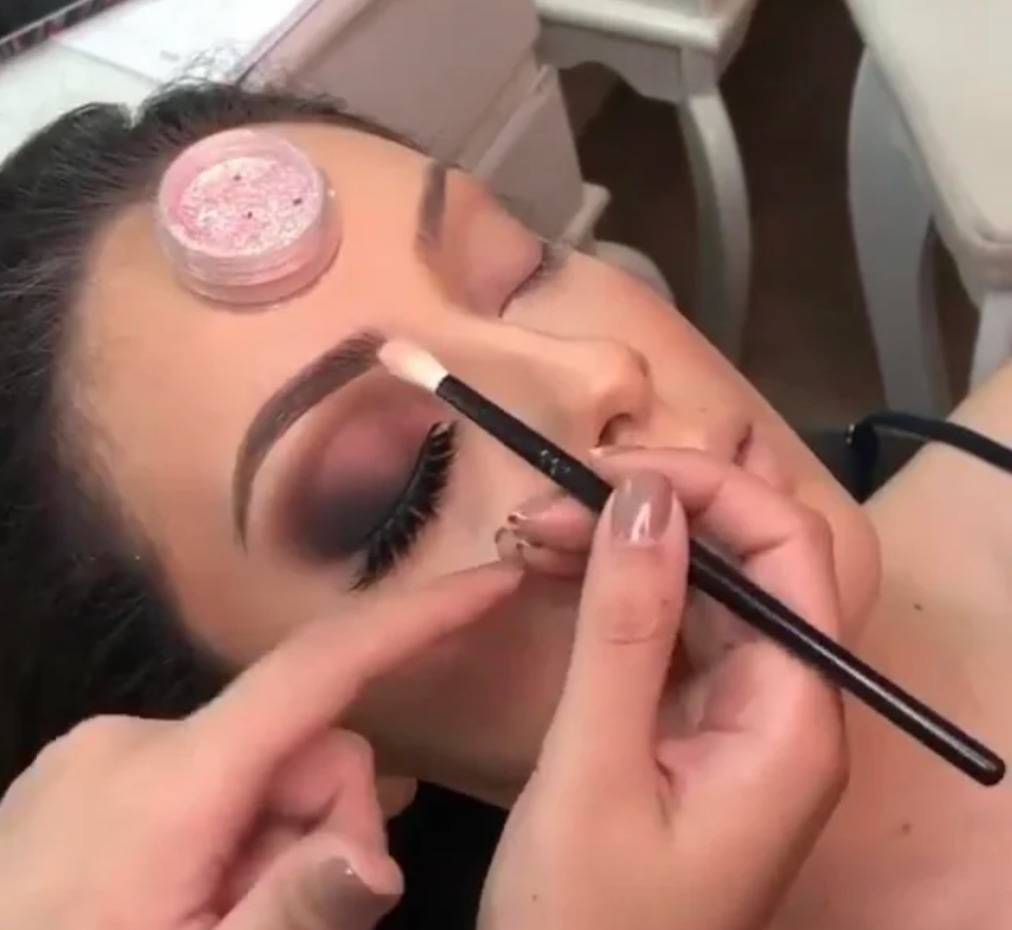 makeup artist is balancing eyeshadow container on client's forehead