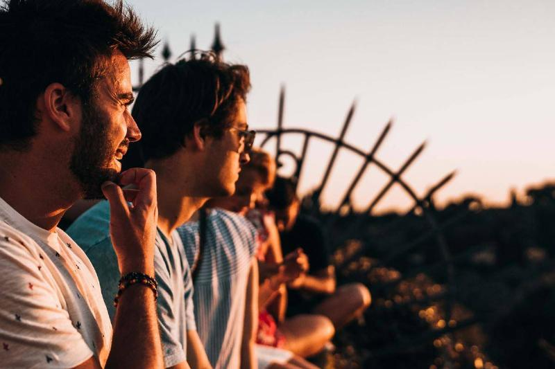group of guys sitting side by side in the sunset