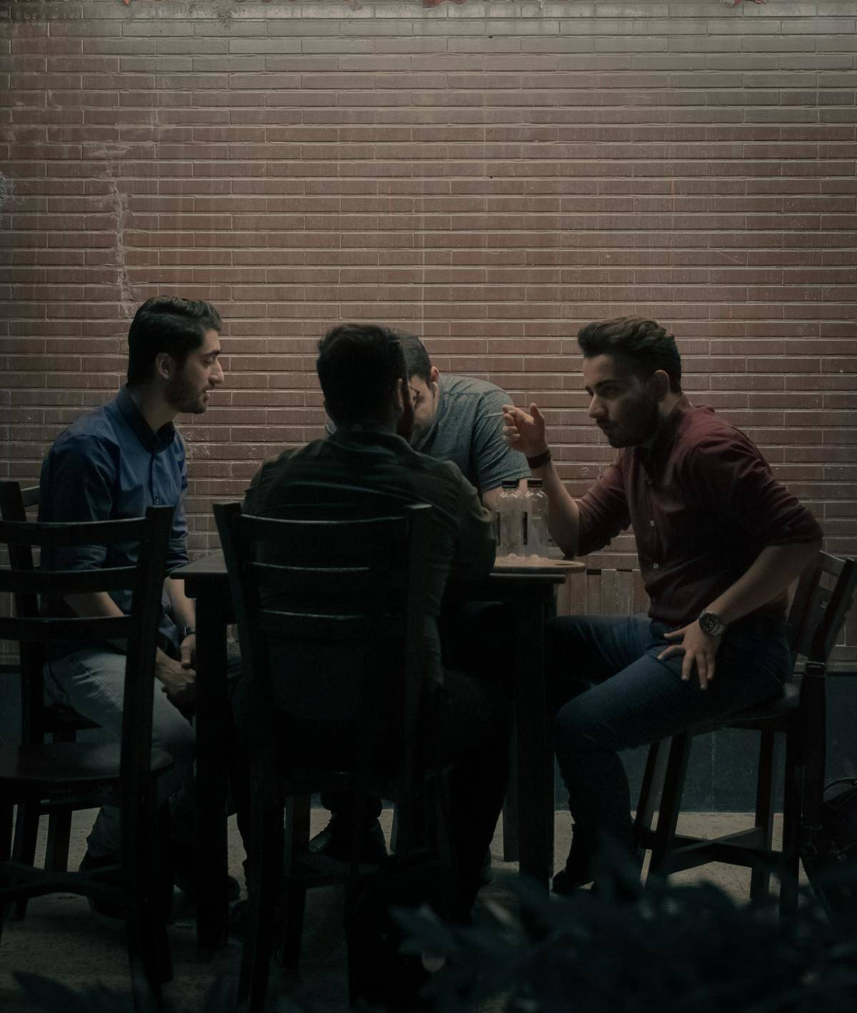 group of men seated at table outside talking at night