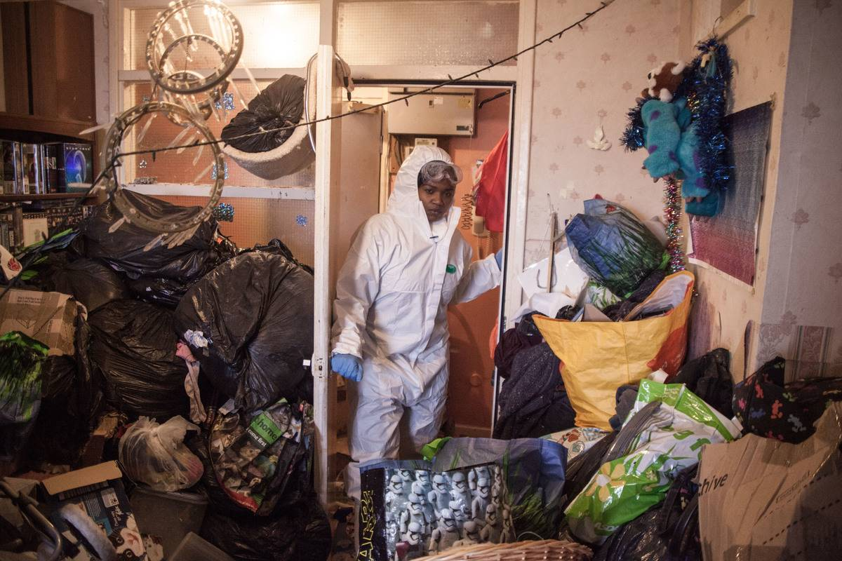 woman in hazmat suit entering cluttered room of hoarder