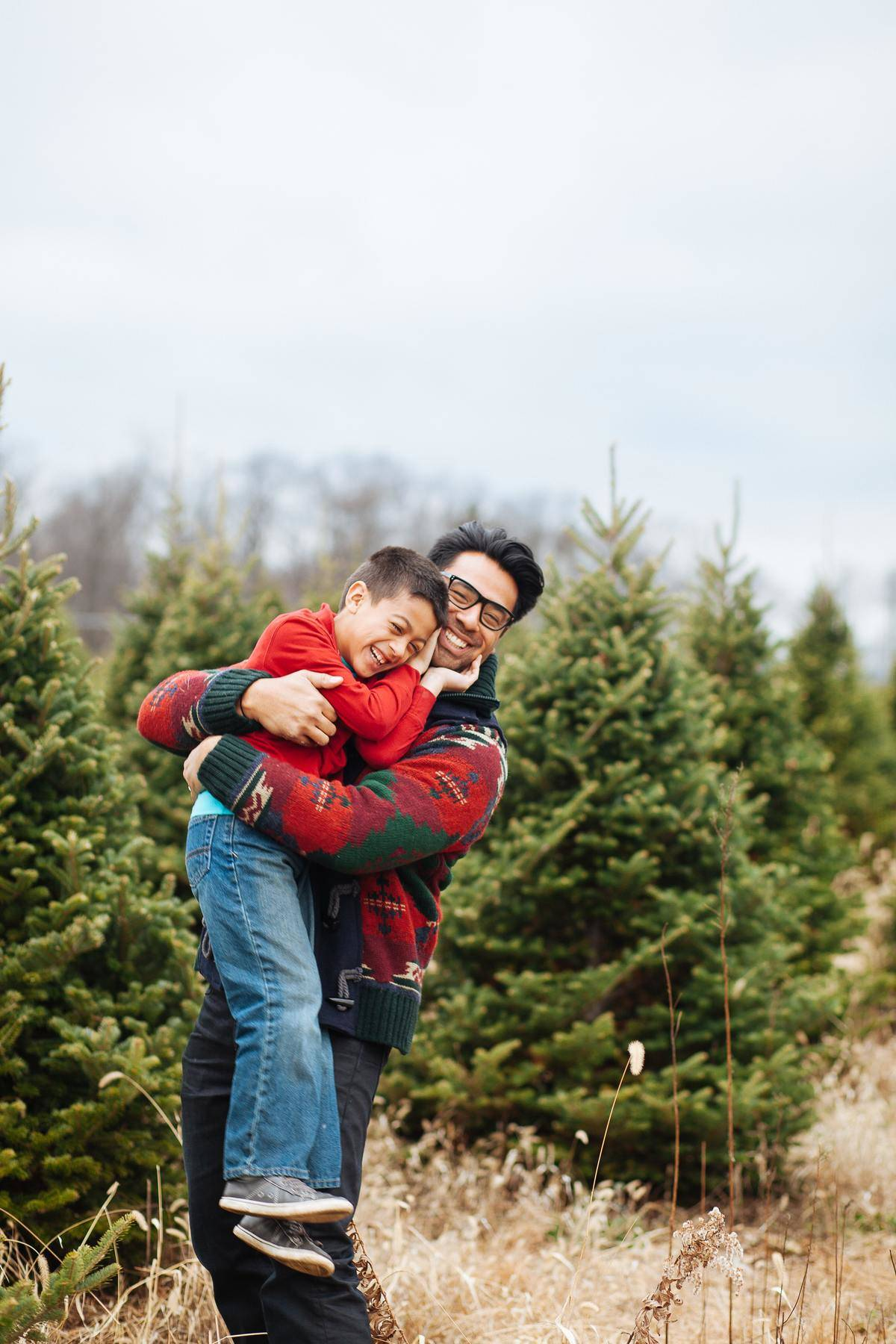 dad hugging his son, both smiling