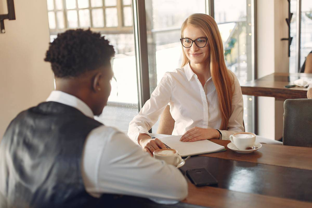 woman writing notes while interviewing man