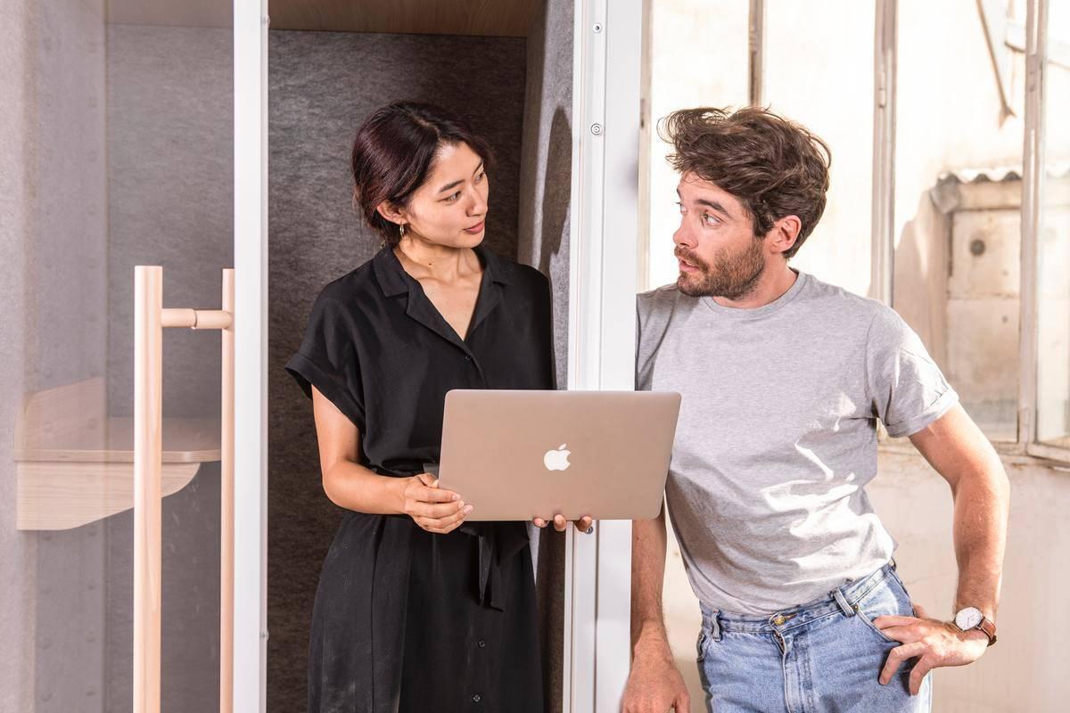 woman showing man something on laptop