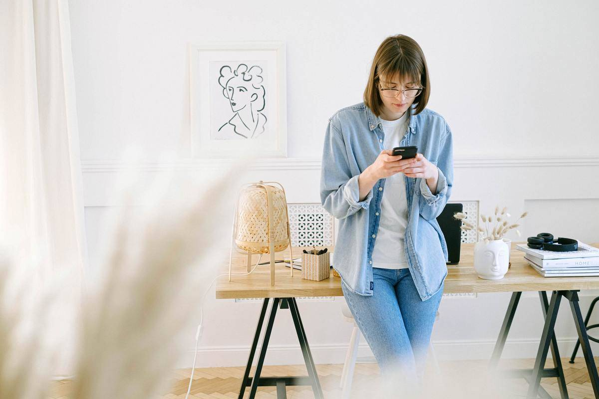 woman leaning on a desk looking down at her phone