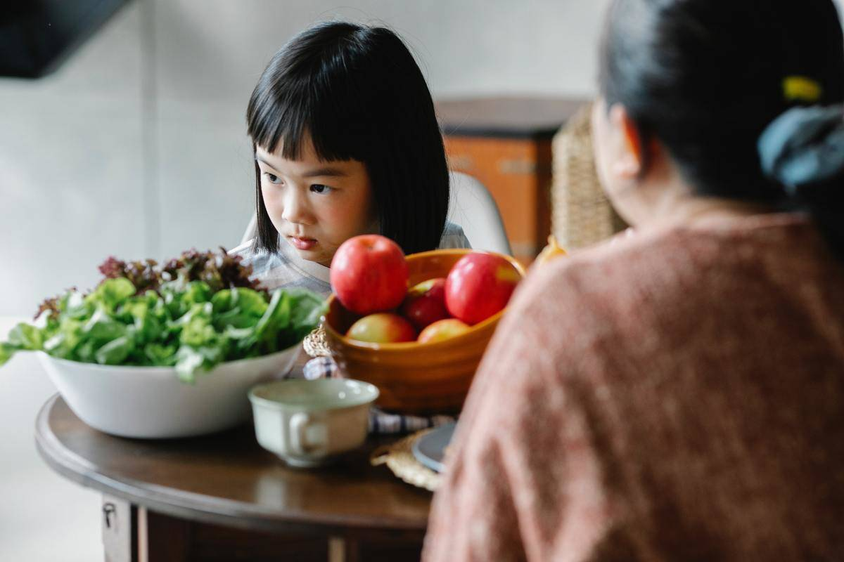 little girl looking upset at dinner table