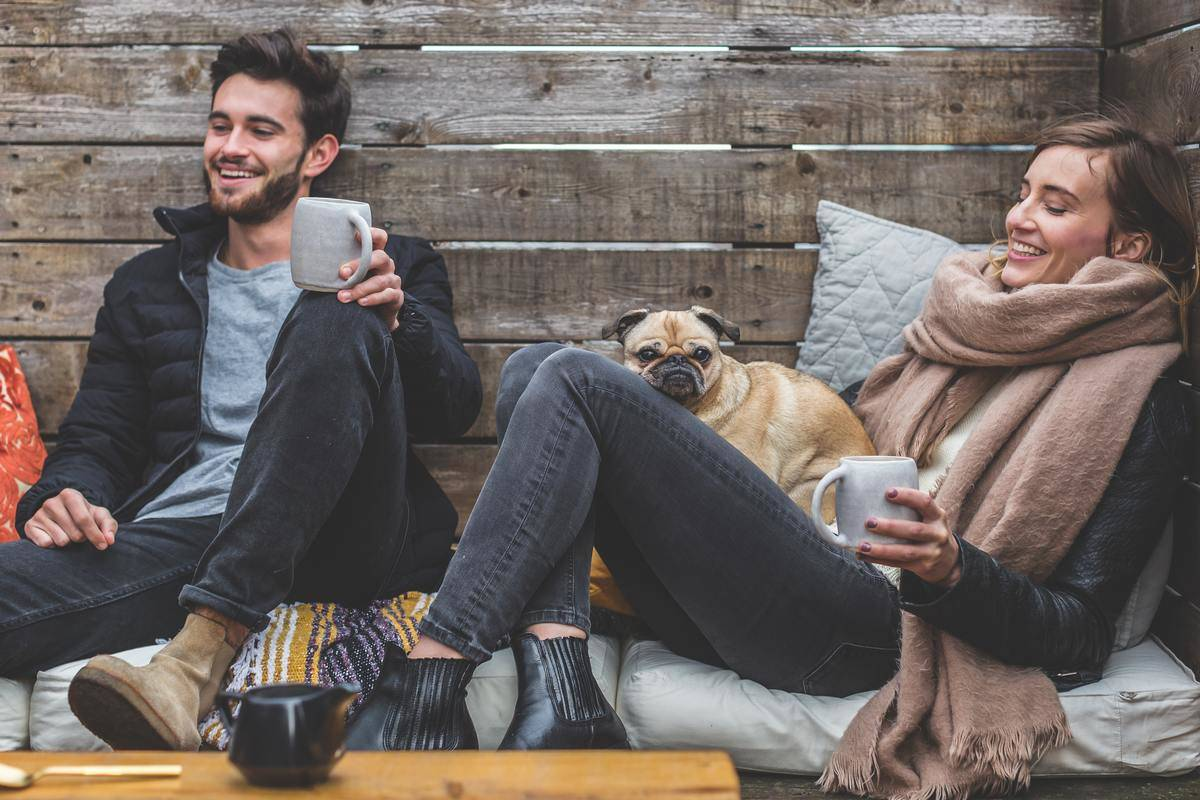 man and woman drink coffee outdoors on bench with dog