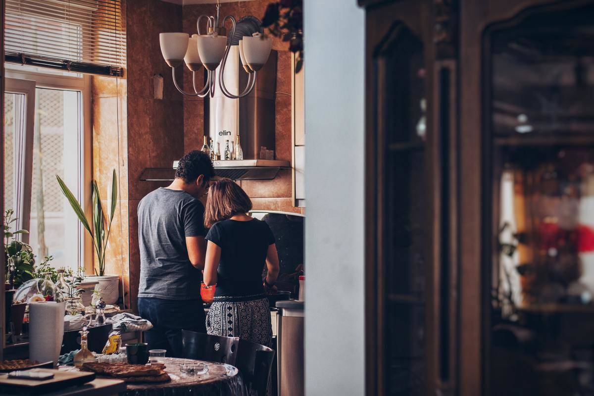 man and woman in the kitchen cooking