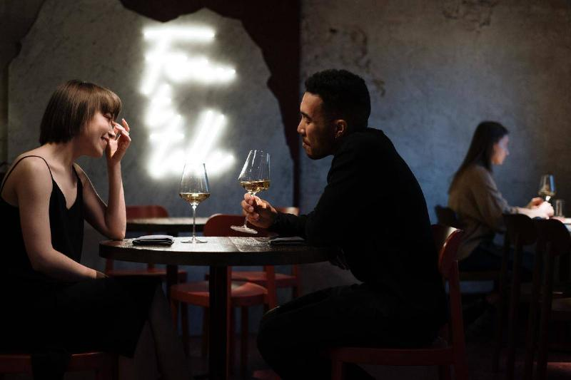 man and woman on a date talking with wine