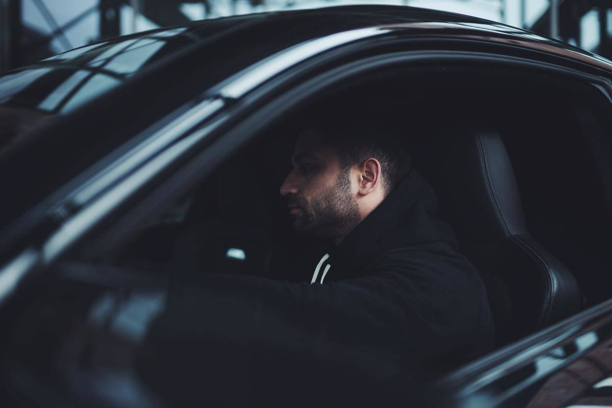 man in dark car seated not driving shadows over face