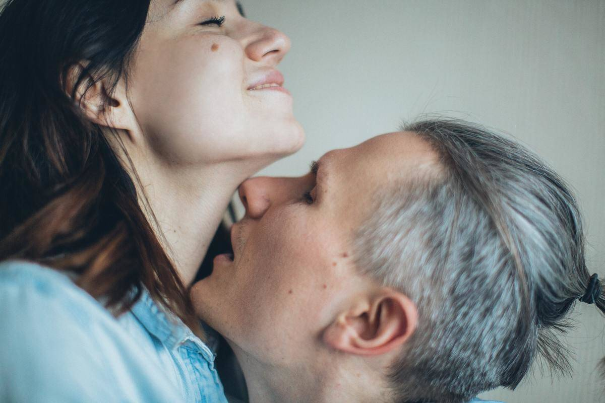 woman smiles as man kisses her neck