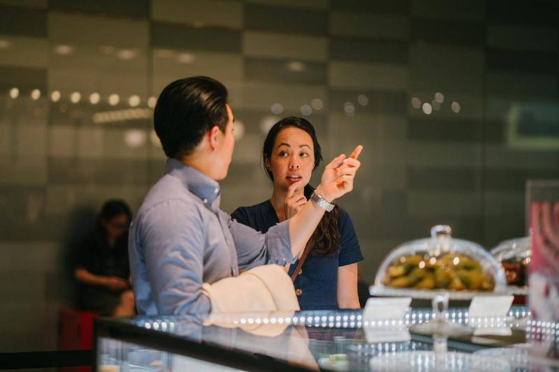 man pointing while talking to woman at coffeeshop counter