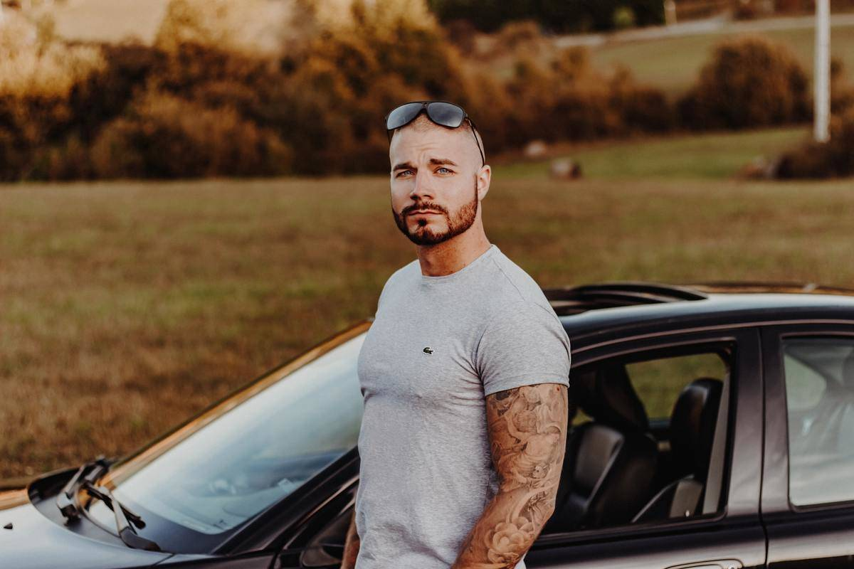 man with arm tattoos poses with parked car