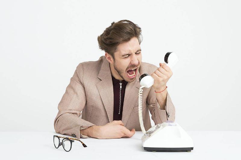 man shouts into phone head