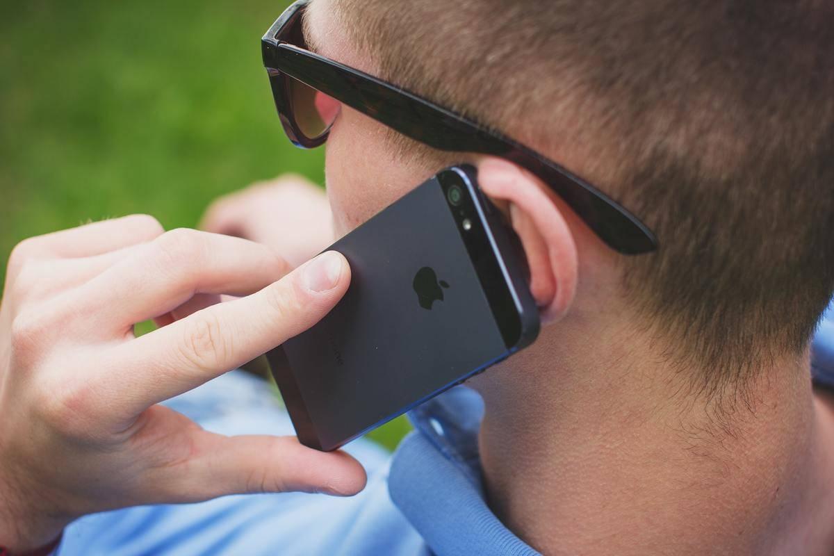 man seated wearing sunglasses talking on black iphone