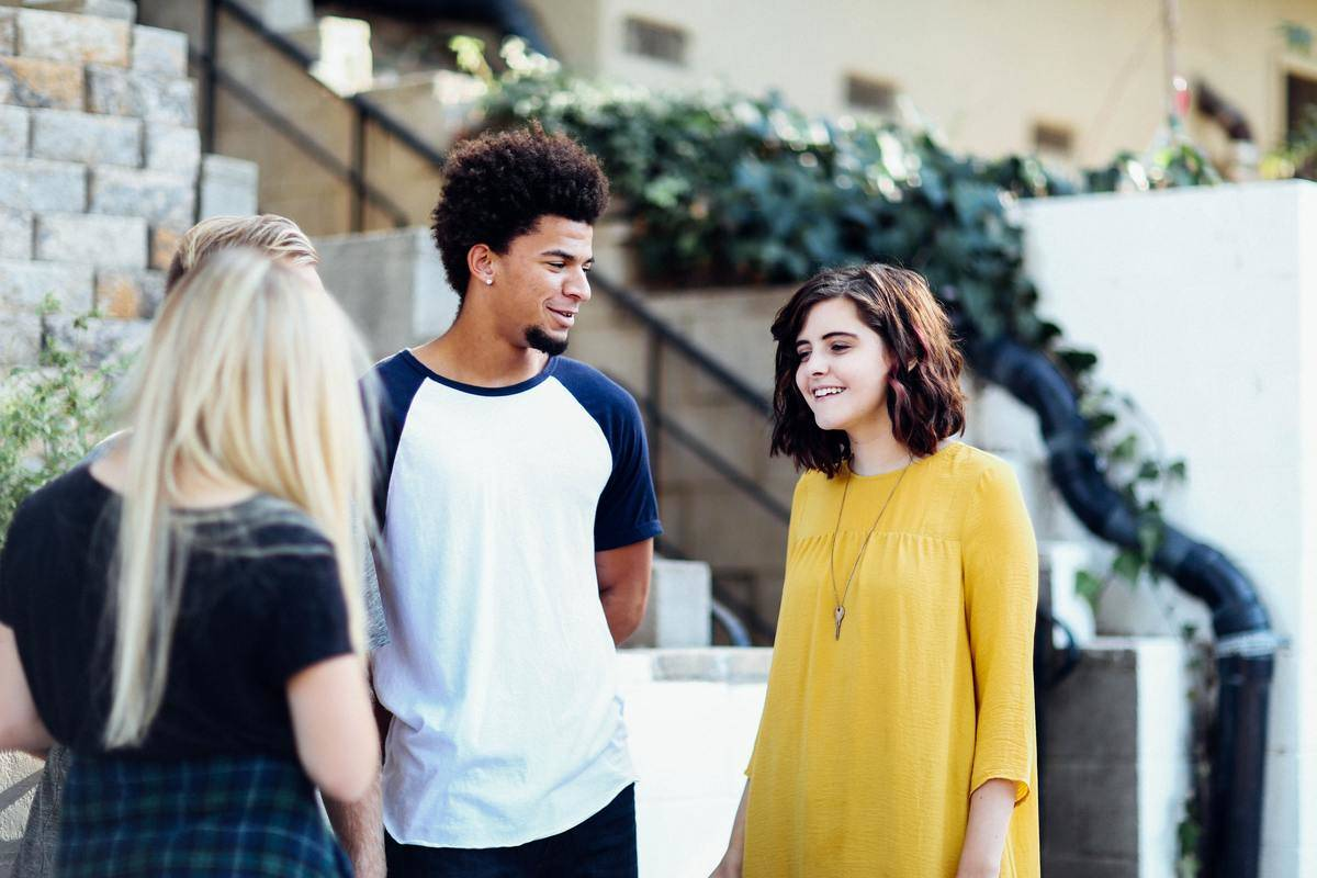 man looking at woman in yellow shirt standing talking to female friend in black shirt