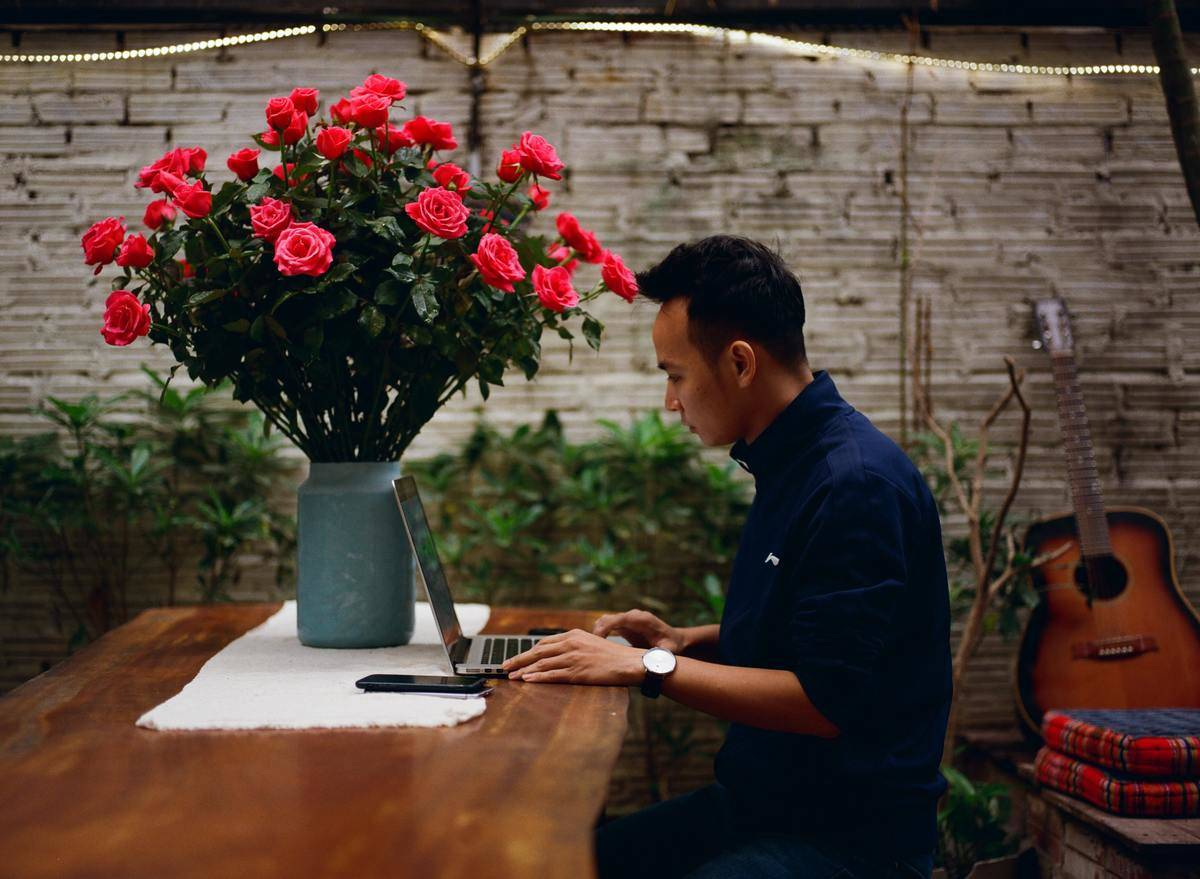 man works on laptop beside giant red bouquet