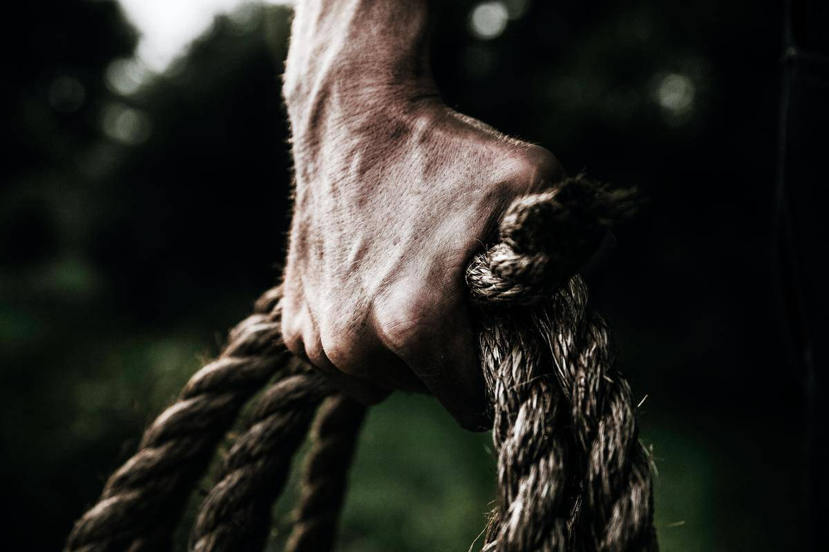 close up of man's hand holding rope