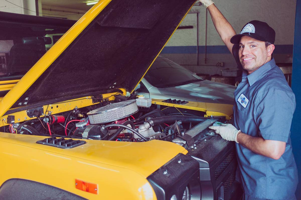 mechanic opens yellow car's hood and smiles