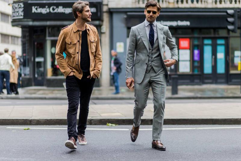 man dressed in nice suit and man in nice casual streetwear walking together